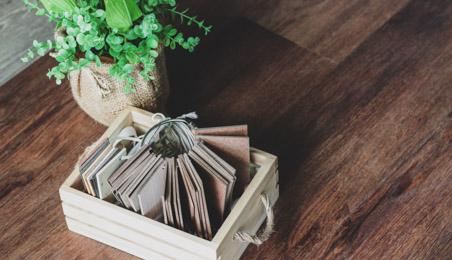 Sol stratifié de teinte bois foncé, boite en bois contenant des échantillons et plante verte