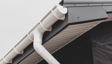Sous-faces en PVC blanc sous une gouttière en PVC blanc