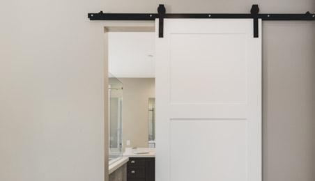 Porte coulissante blanche sur système apparent en métal noir