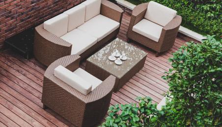 Terrasse en bois, ensemble de fauteuils, table et canapé en rotin et tissu crème