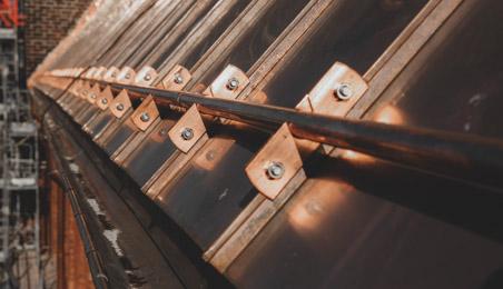 Bord de toiture en cuivre en gros plan avec plaques et barres de fixation