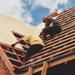 Couvreurs posant des panneaux de bois sur un toit