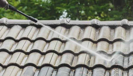Couvreur nettoyant un toit en tuiles canal brunes avec un jet haute pression