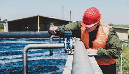 Ouvrier manipulant une vanne sur une cuve de traitement des eaux