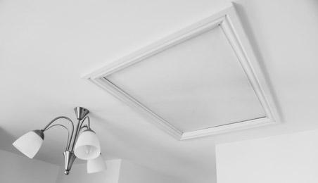 Trappe d'accès dans un plafond blanc à côté d'une suspension blanche