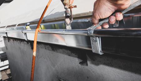Zingueur posant une gouttière avec un fer de couvreur