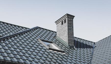 Toit en tuiles de béton grises avec velux et cheminée