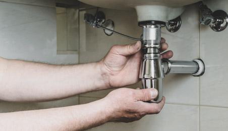 Plombier installant un siphon chromé sous un évier