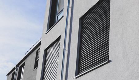 Volet roulant en PVC noir abaissé sur une façade grise