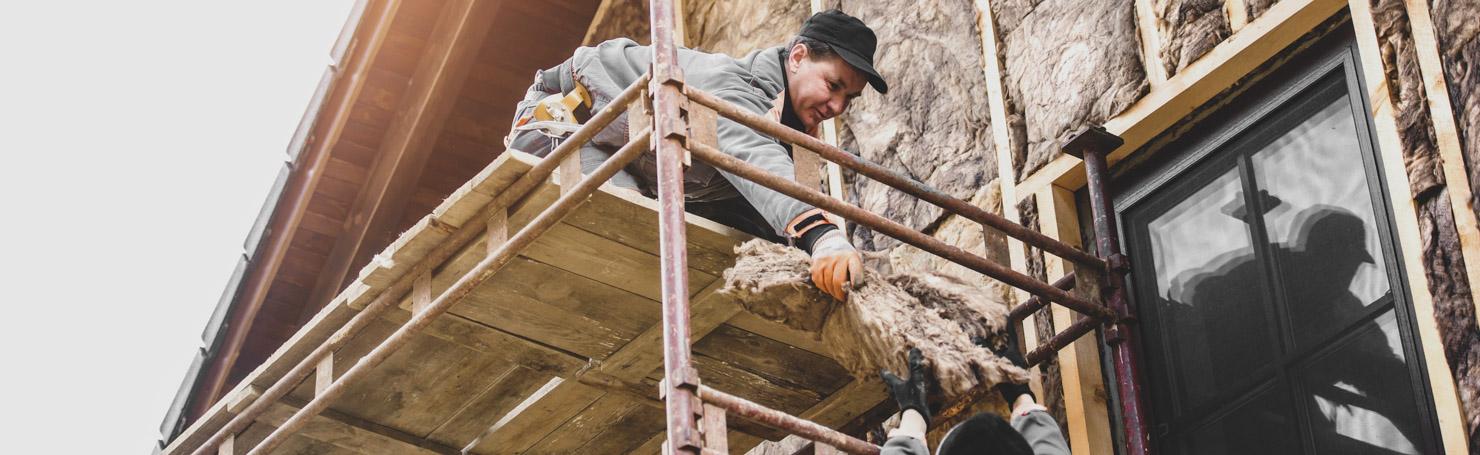 Ouvrier posant de la laine de roche en façade