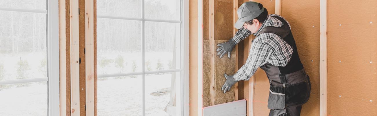 Ouvrier posant des panneaux d'isolant sur un mur intérieur