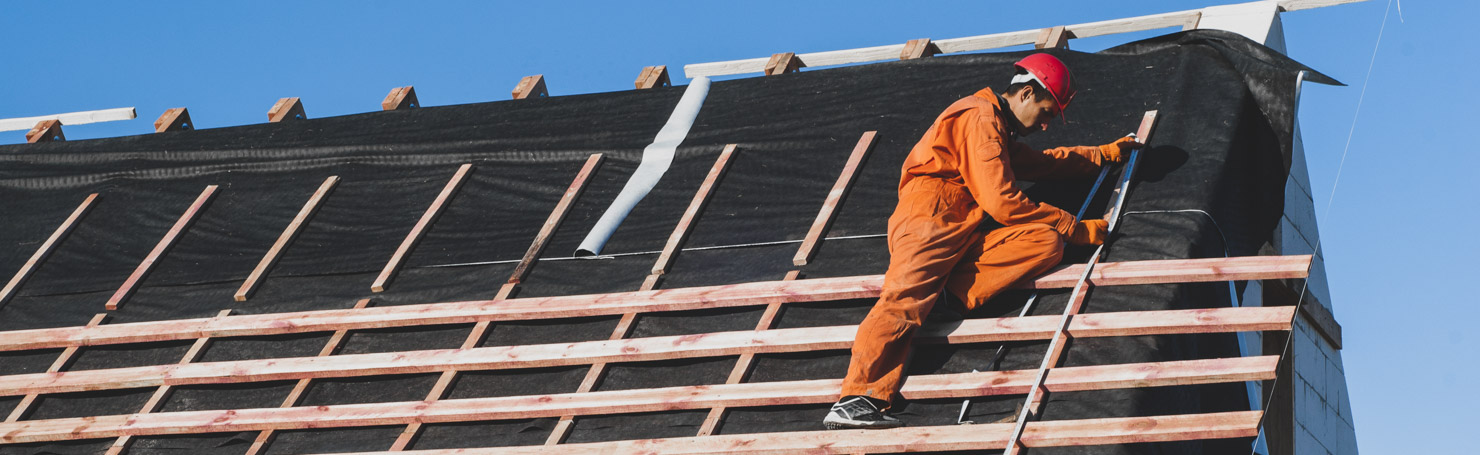 Couvreur posant des liteaux sur un toit en construction