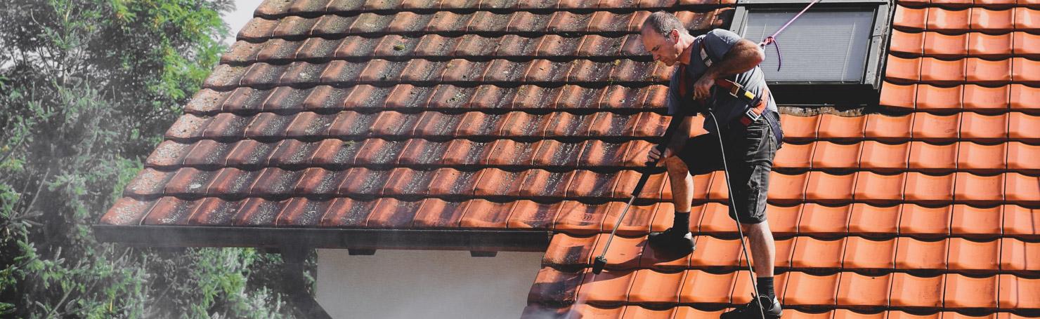 Couvreur nettoyant un toit de tuiles avec un nettoyeur haute pression