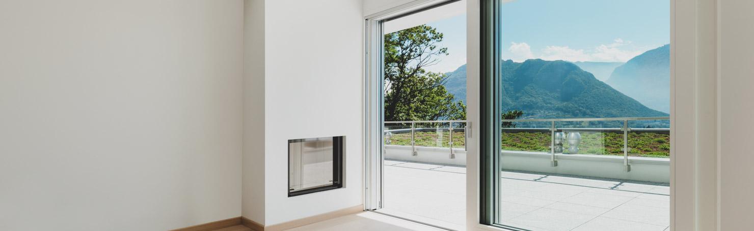 Baie vitrée en aluminium blanc ouvrant sur un balcon