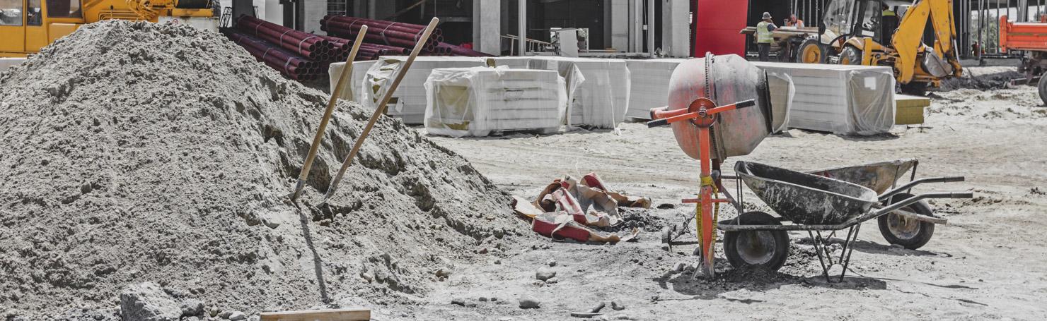 Bétonnière et brouette près d'un tas de sable