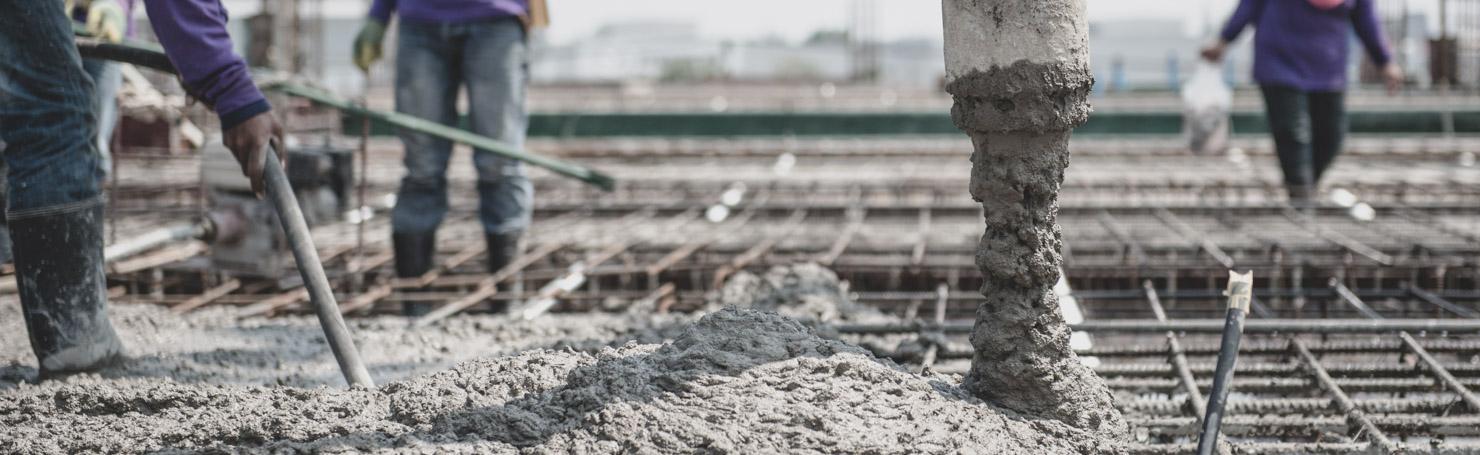 Ouvriers coulant du béton sur des armatures de plancher en acier