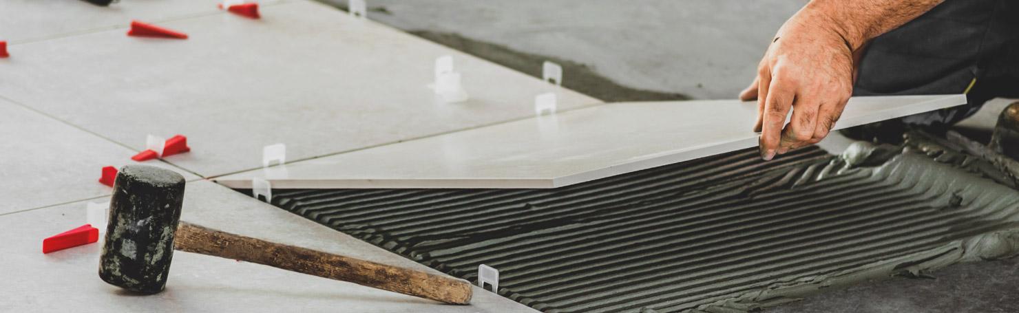 Artisan posant un carreau de carrelage sur une couche de colle