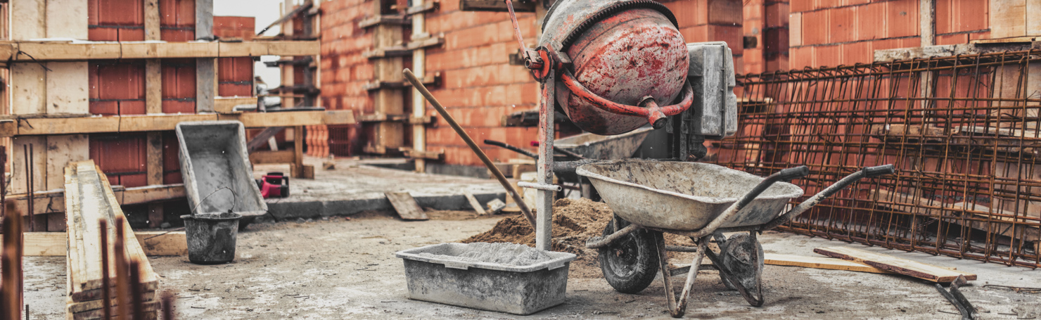Brouette et bétonnière au premier plan devant un chantier