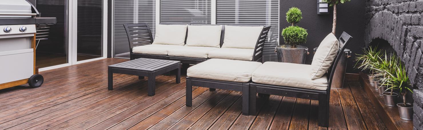 Terrasse en bois foncé, fauteuil et canapé de jardin en tissu blanc et métal noir