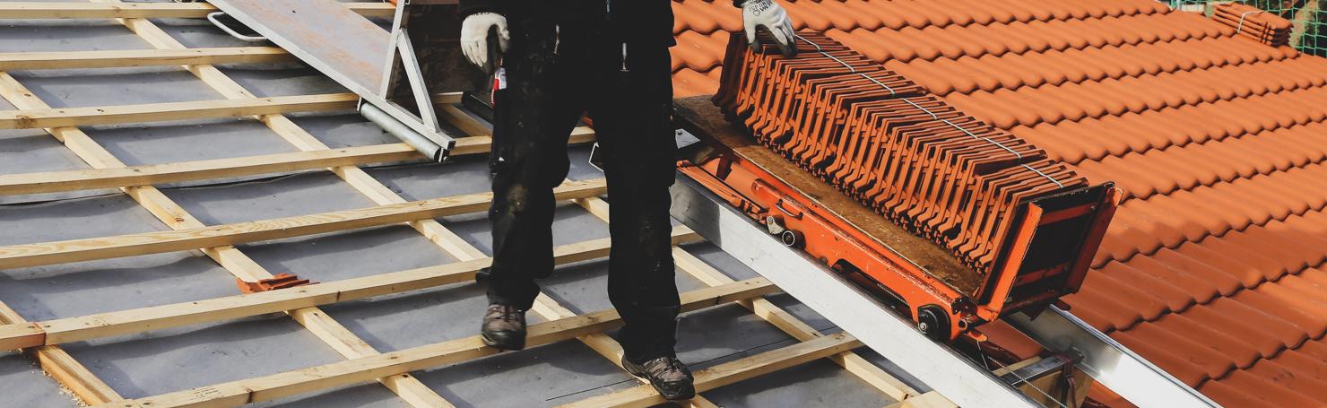 Couvreur debout sur un toit de tuiles en construction avec un chariot rempli de tuiles à côté de lui